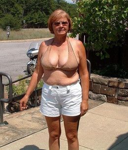 Dissolute granny sunbathing naked on..